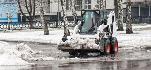 loader removing snow outside on the street
